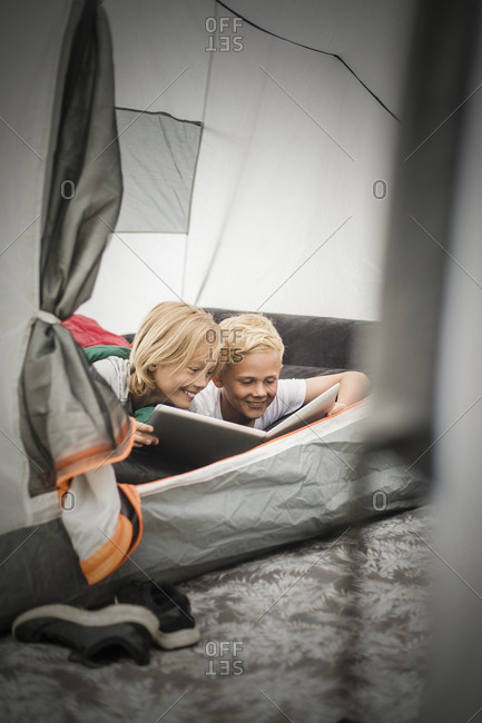 Smiling siblings using digital tablet while lying in tent at camping site