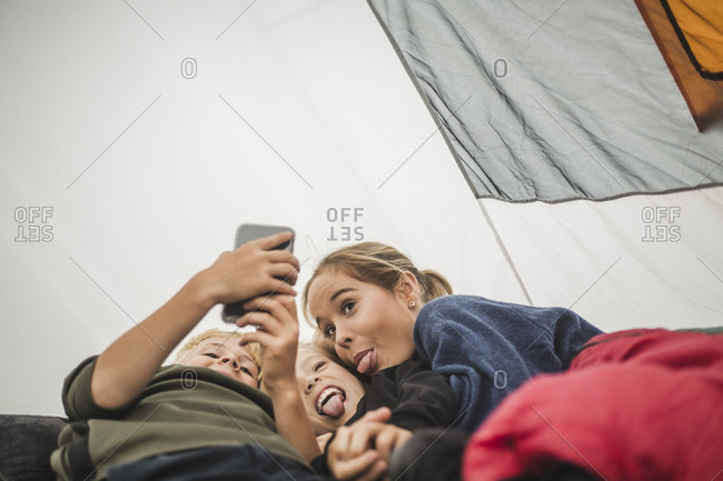 Siblings making face while taking selfie in tent