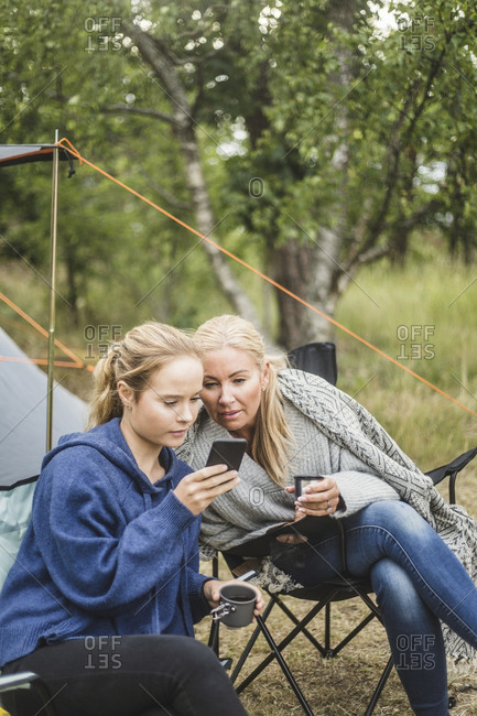 Mother and daughter looking at smart phone while having coffee in campsite