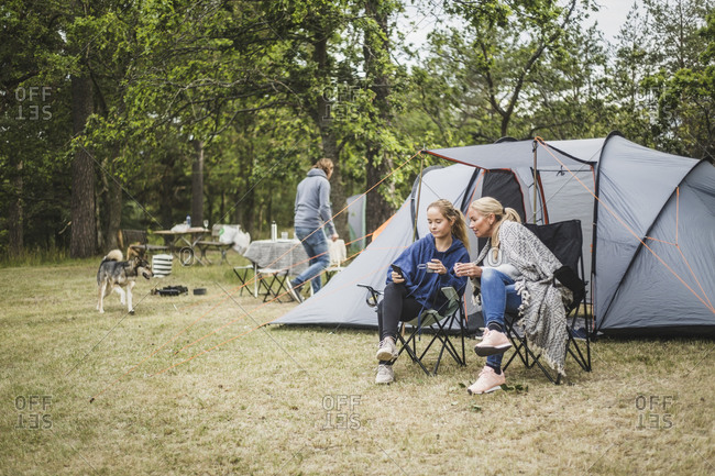 Mother and daughter having coffee while looking at mobile phone in campsite