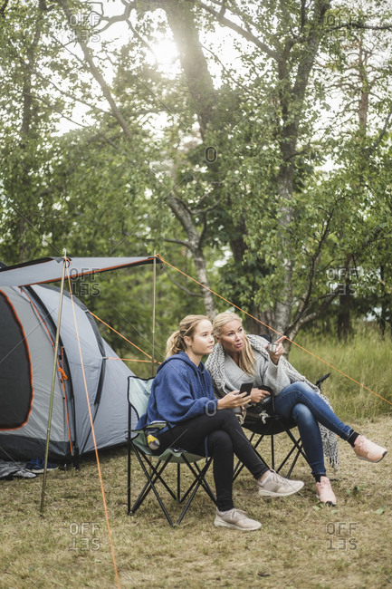 Full length of woman talking to daughter while sitting at campsite