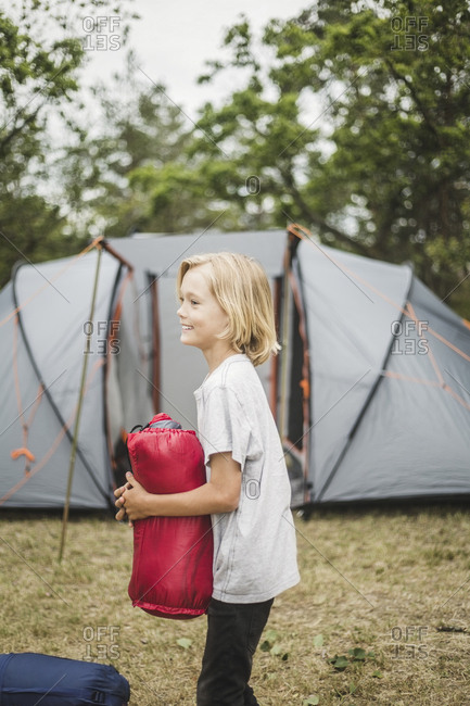 Side view of smiling boy holding tent while standing against tent