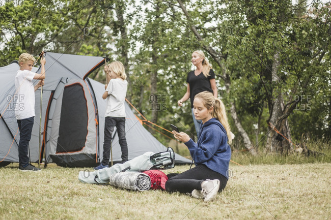Teenager text messaging on mobile phone while family pitching tent