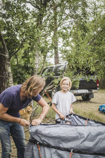 Father and daughter talking while pitching tent at camping site