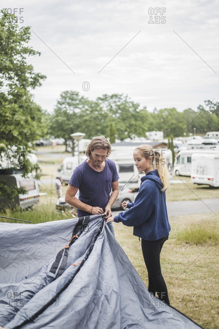 Teenage girl assisting father in pitching tent at campsite