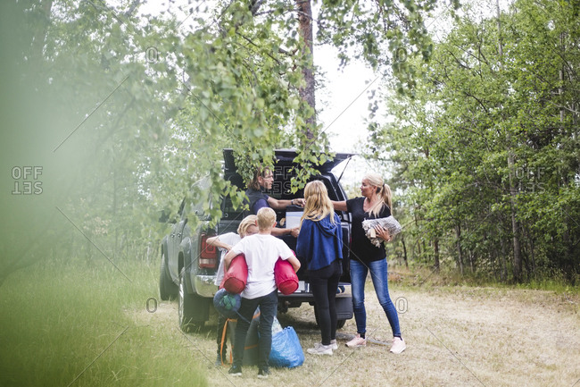 Parents with children unloading luggage from car at camping site during vacation