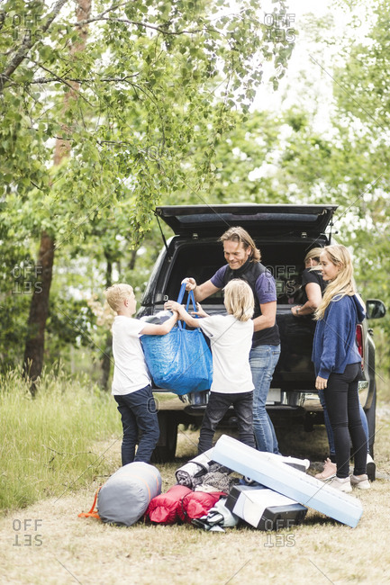Children assisting parents in unloading luggage from car trunk at camping site