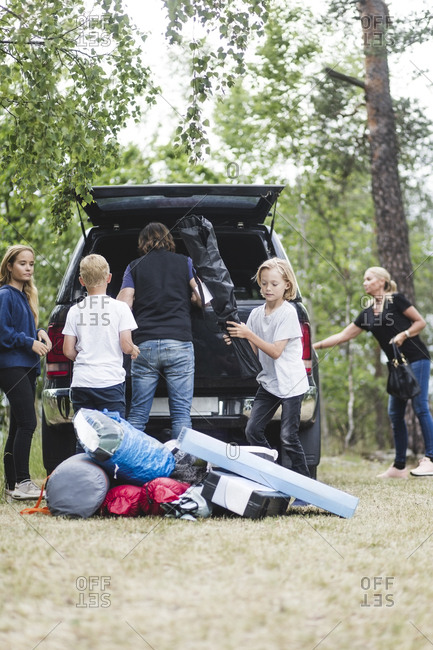 Camping family unloading luggage from car trunk at forest
