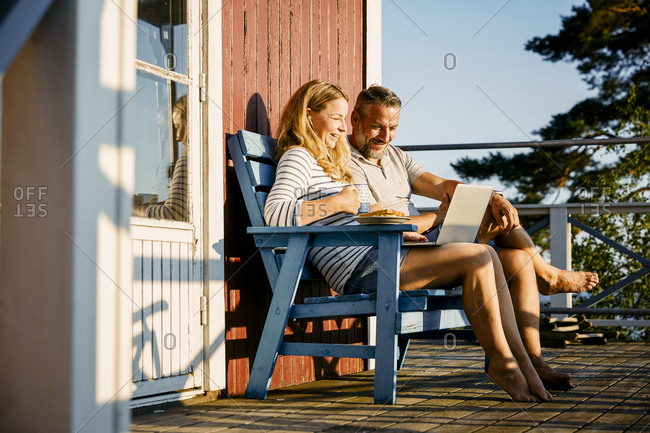 Smiling couple using laptop while having breakfast at porch in log cabin