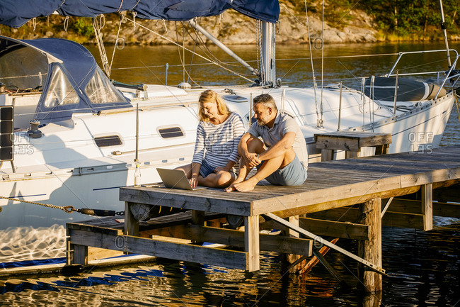 Couple discussing over laptop while sitting on pier by yacht during sunny day