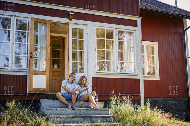 Couple looking at smart phone while sitting on steps outside log cabin