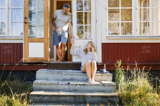 Male partner giving glass of water to woman while standing in doorway at log cabin