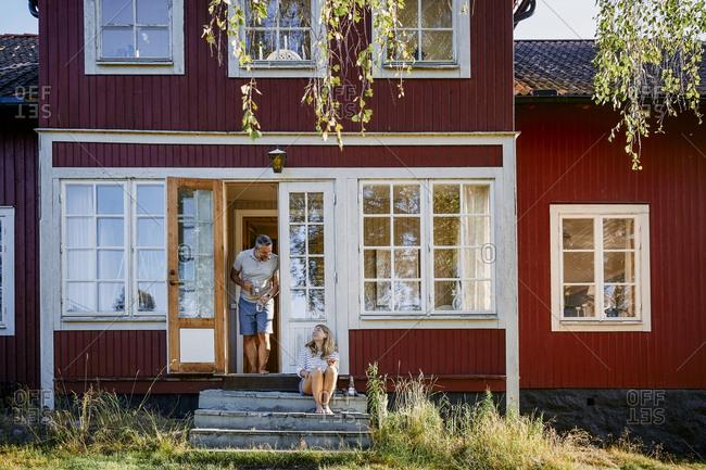Man and woman talking at entrance of log cabin
