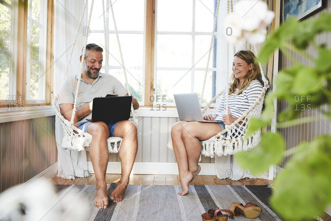 Smiling couple using laptops while sitting on rope swing in log cabin