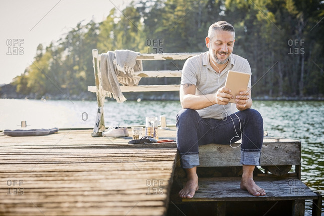 Smiling mature man using digital tablet with in-ear headphones while sitting on jetty over lake