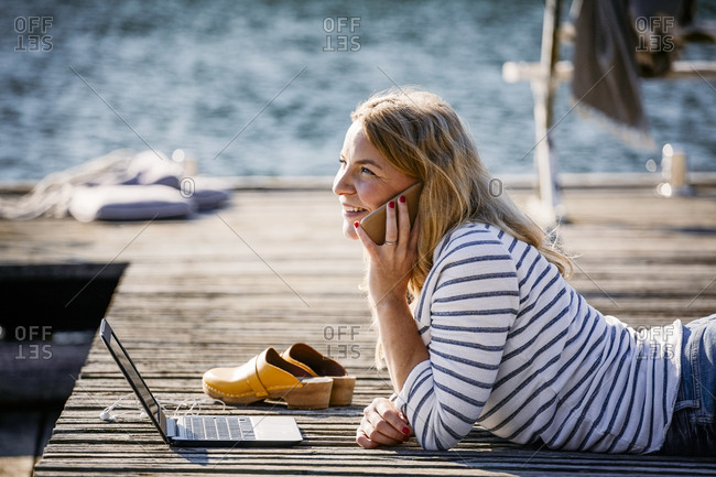 Smiling female with laptop talking on smart phone while lying over wooden pier