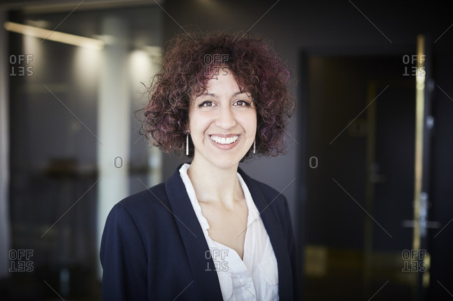 Portrait of smiling female legal professional with curly hair at office