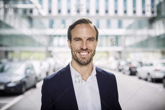 Portrait of smiling mid adult lawyer standing against office