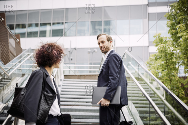 Low angle view of lawyer talking to coworker while standing on steps at office