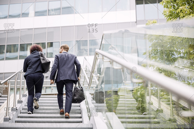 Rear view of business coworkers walking on steps towards office