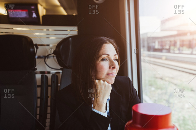 Thoughtful businesswoman looking through window while traveling in train