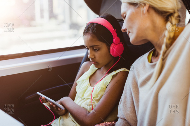 Mother looking at daughter watching movie on smart phone while traveling in train