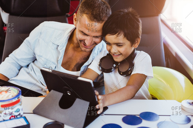 Smiling father and son using digital tablet while sitting in train