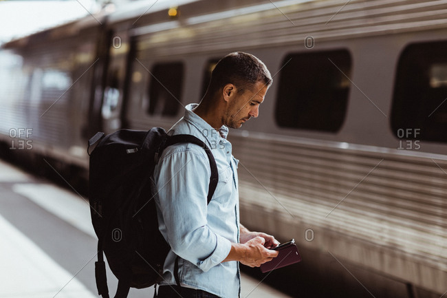 Tourist with backpack using smart phone on railroad station platform