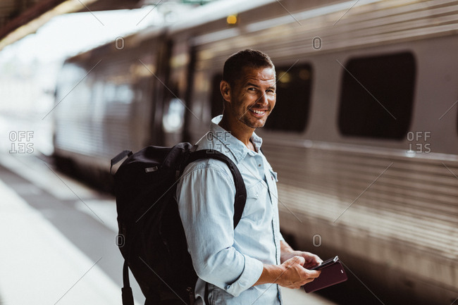 Portrait of smiling tourist with backpack holding smart phone on platform at train station