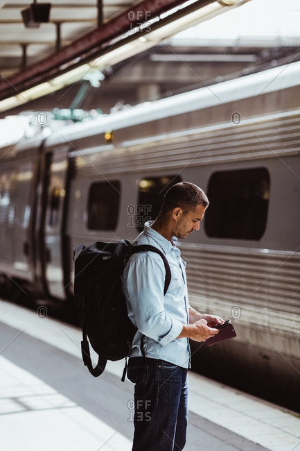 Mid adult man with backpack using mobile phone while standing by train on platform