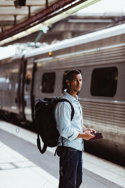Thoughtful man with backpack holding smart phone while looking at train on platform