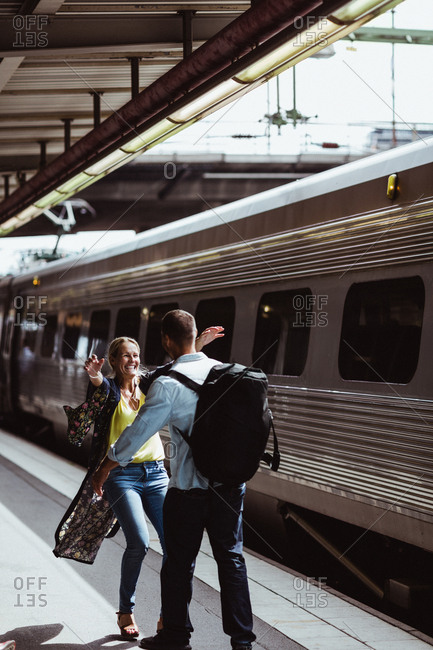 Cheerful couple embracing by train on railroad station platform