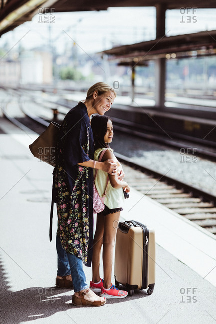 Smiling mother and daughter waiting on platform at train station
