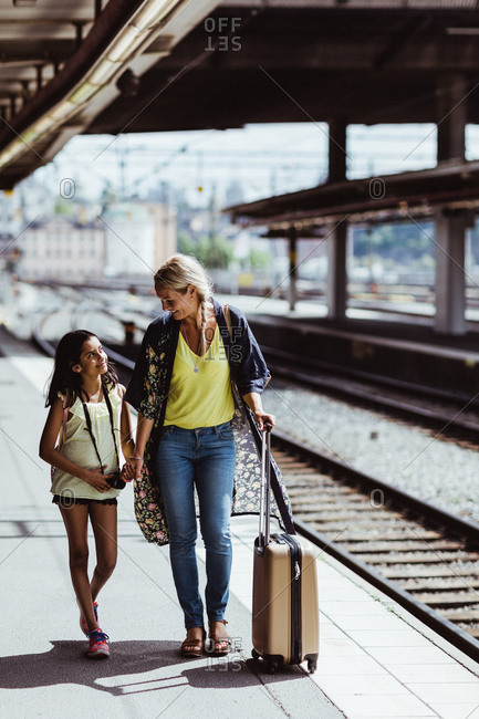 Full length of mother and daughter with luggage walking at railroad station