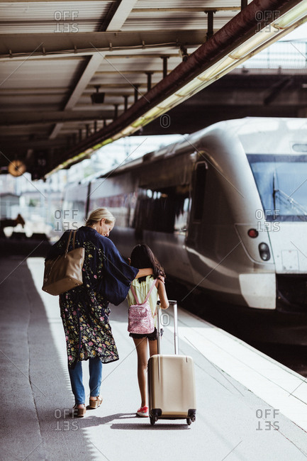 Full length of mother and daughter with luggage walking on platform at train station