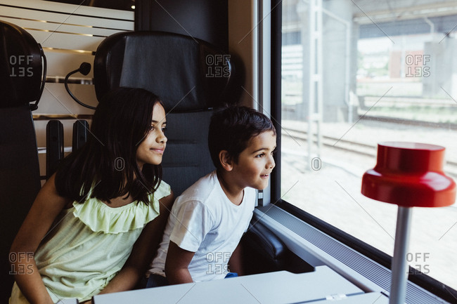 Siblings looking through train window while traveling together