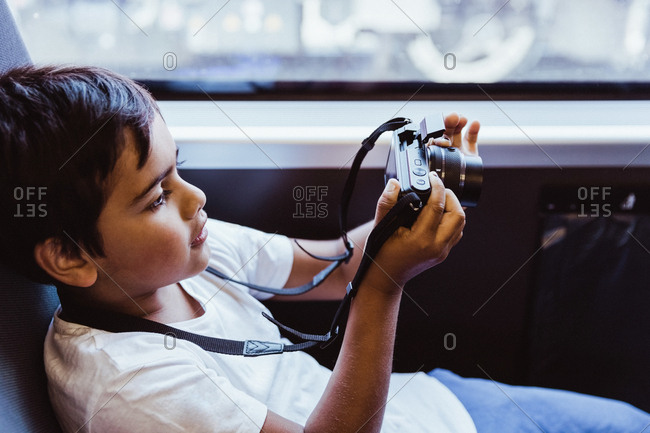 Boy photographing through camera while sitting in train