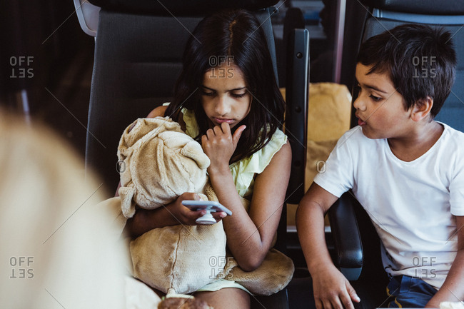 Boy looking at sister using smart phone while traveling in train