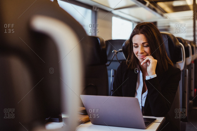 Smiling businesswoman using laptop while sitting in train