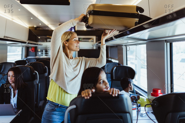 Woman arranging luggage on shelf while traveling with children in train