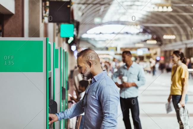 Businessman buying ticket at railroad station platform