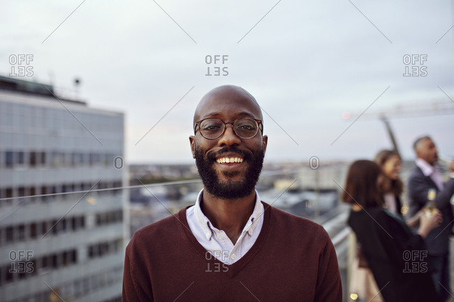 Portrait of smiling businessman wearing eyeglasses enjoying at office party