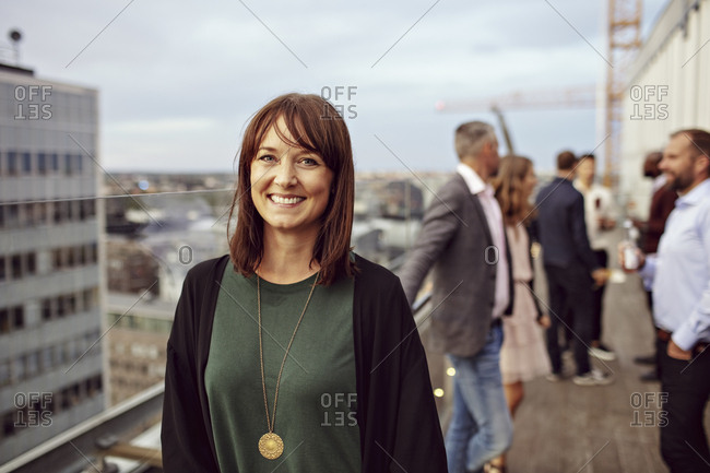 Portrait of smiling businesswoman with colleagues in background standing on terrace during party