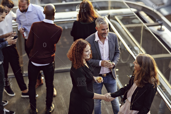 High angle view of businesswoman doing handshake and greeting while partying with coworkers after work on terrace