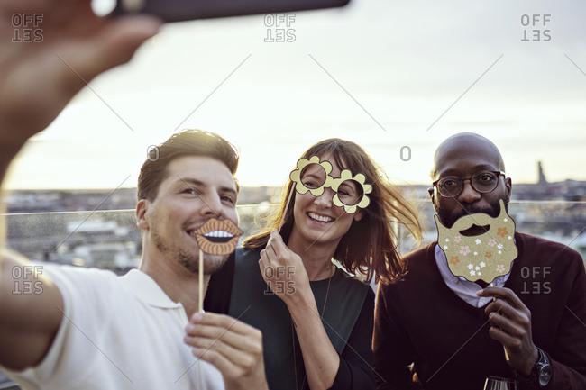 Smiling business colleagues enjoying with props while taking selfie at party on terrace