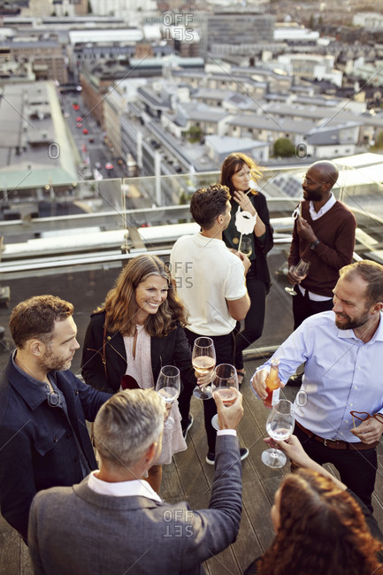 High angle view of coworkers toasting wineglasses while partying at building terrace