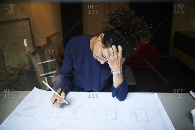 Female tensed architect working at table in office