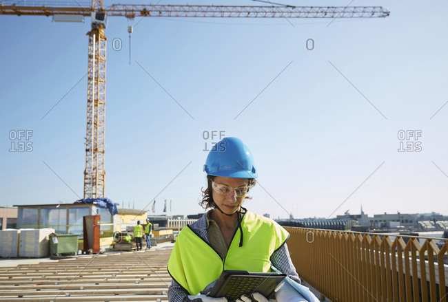 Confident female architect in reflective clothing using digital tablet at construction site against clear sky