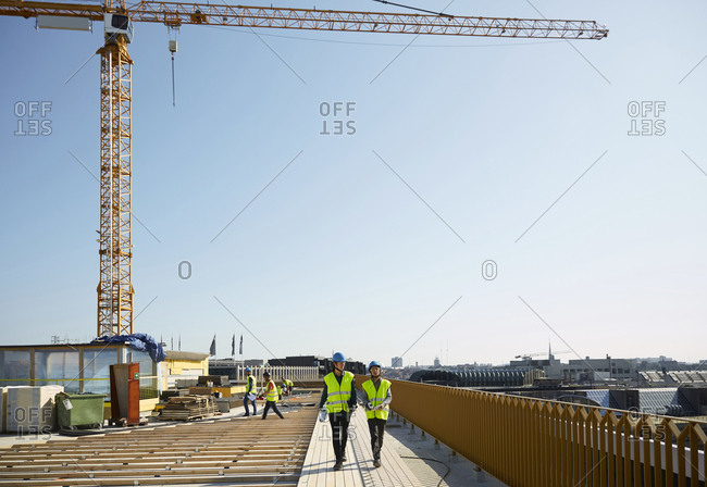 Female coworkers walking at construction site against clear sky