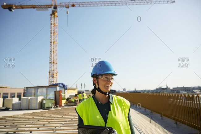 Smiling female engineer in reflective clothing with digital tablet at construction site against clear sky